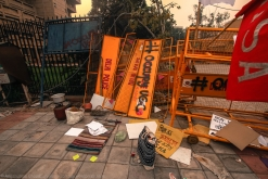"""The clutter at the protest site - either in a realistic or surrealistic way, looks like """"meaningful mess"""". These dented and broken barricades are remnants of the second or third night after the beginning of the occupation, when the students - frustrated by the nonchalance of the authorities and desperate for at least some explanation - tried to force themselves into the inner compound to meet the officials. They were pushed back, very magnificently, by a relentless rain of police batons. These somewhat sordid remnants form the background to a bunch of life-essentials - like a cooking stove, a boiling pot - necessary for a prolonged stay at the site."""