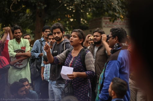 """A student organiser spells out the course of action for the evening, intimating to the protestors their collective decision to stay put in front of the barricades till they are not given an chance to submit their deposition to an MHRD official in-person. However, as declared by her in succinct terms, the absolute priority was to demand a personal meeting with Ms. Smriti Irani who had spent a few minutes with the students during their first march to the ministry. In an unrelenting speech, she reiterated how the excessive police cover was anticipated as the administration regularly sends their forces after university students, at least twice a month or so, """"for mere target practice with their lathis""""."""